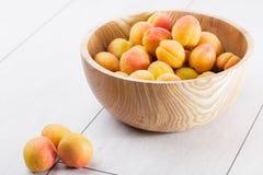fruits organiques mûrs d'abricots dans la cuvette en bois d'arbre de cendre sur un fond en bois blanc image libre de droits