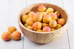 fruits organiques mûrs d'abricots dans la cuvette en bois d'arbre de cendre sur un fond en bois blanc photo stock