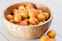 fruits organiques mûrs d'abricots dans la cuvette en bois d'arbre de cendre sur un fond en bois blanc photos stock