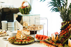 Fruits and pastry stand on the buffet behind empty crockery.  Royalty Free Stock Photo