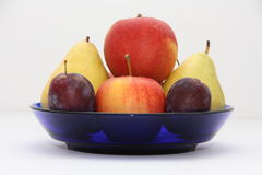 Fruits. Pear apple plum plate blue Stock Image
