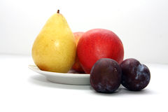 Fruits. Pear apple plum plate fruit autumn Royalty Free Stock Image