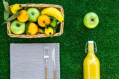 Fruits for picnic. Apple, banana, tangerine on tablecloth on green grass background top view Royalty Free Stock Photography