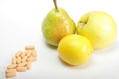 Fruits or pills. Fruits and vitamin pills on a light background Royalty Free Stock Photography