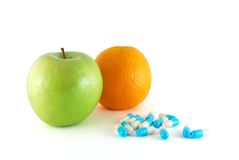 Fruits and pills. Apple, orange and blue pills on the white background stock images