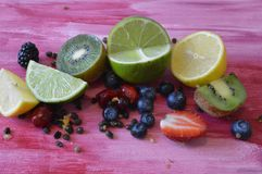 Fruits on the pink wooden board. Tropical fruits on purple wooden board, with seeds and berries royalty free stock photography