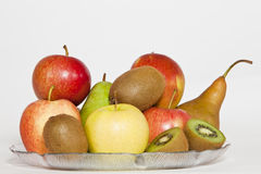 Fruits in a plate. Some Fruits, with a sliced Kiwi in front, in a plate stock image