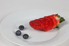 Fruits plate. Plate with three blueberry  and strawberry slices Royalty Free Stock Photos