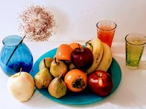 Fruits on plate with glass ,vase still life ,apples , bananas ,pears ,photo art. Vase Plate Glass Red Yellow Blue Color modern photo art design Fruits on blue royalty free stock photography