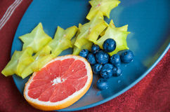 Fruits on a plate- Grapefruit, star fruit and blueberries ready to eat Stock Images