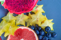 Fruits on a plate- Red dragon fruit, grapefruit, star fruit and blueberries ready to eat Royalty Free Stock Photos