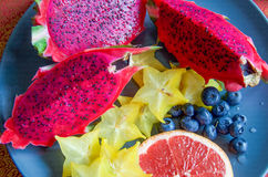 Fruits on a plate- Red dragon fruit, grapefruit, star fruit and blueberries ready to eat Royalty Free Stock Photography
