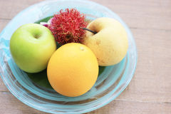 Fruits in plate on wood background. Fruits in plate on wooden background stock photography