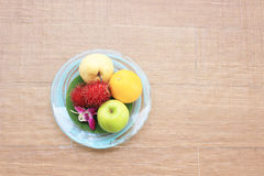 Fruits in plate on wood background Royalty Free Stock Photo