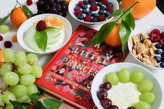 Fruits on Plates Beside Red Book Stock Images