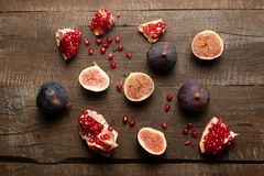 Fruits pomegranate and figs against old wooden table. Flat lay view of some figs and pieces of pomegranate on old brown wooden table royalty free stock image
