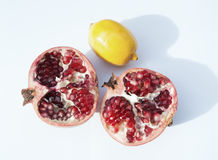 Fruits pomegranate and lemon. Two halves of pomegranate and lemon on a white background Stock Photography