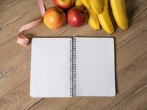 Fruits pomme et bananes, carnet vide et centimètre sur la table en bois, vue supérieure, flatlay photographie stock libre de droits