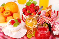 Fruits preserves. Various fruits preserves in jars and fresh fruits on table Royalty Free Stock Image