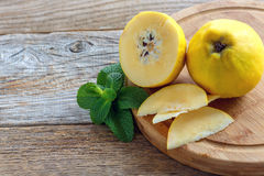 Fruits quince and mint. Royalty Free Stock Photos