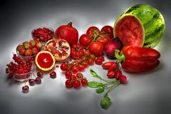 Fruits red colored shining in the dim light of dark gray background. S and all are  identified by the color red Royalty Free Stock Photography