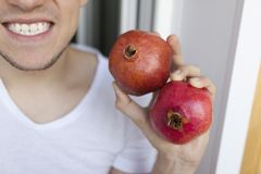 Fruits of red pomegranates in the hands of a close-up man who smiles Royalty Free Stock Images