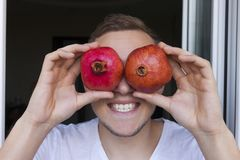 Fruits of red pomegranates in the hands Royalty Free Stock Photos