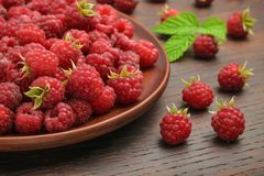 Fruits of red raspberries in a plate and on a table, shot near. Healthy snack.  Stock Image