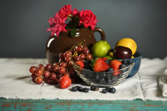 Fruits on Table. Fruits and red roses on table over gray background royalty free stock photos