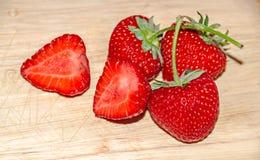 Fruits rouges de fraises et fond en bois rustique de demi fraise Image stock