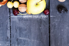 Fruits on rustic table and inscription healthy food. Royalty Free Stock Photos