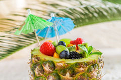 Fruits salad in pineapple with cocktail umbrellas Royalty Free Stock Photo