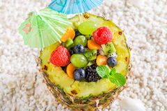 Fruits salad in pineapple with cocktail umbrellas Stock Photos