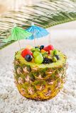 Fruits salad in pineapple with cocktail umbrellas. On white pebbles royalty free stock images