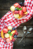 Fruits salad. Served in glasses on wooden background,from above stock image
