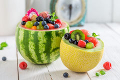 Fruits salad in watermelon and melon with berry fruits. On white table stock image