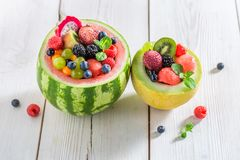 Fruits salad in watermelon in summer. On white table Royalty Free Stock Images
