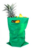 Fruits Shopping. Fruits in green shopping bag on white isolated background royalty free stock image