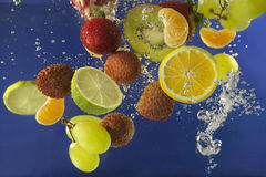 Fruits splash in water with bubbles Stock Image