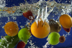 Fruits splash in water with bubbles Stock Photos