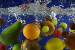 Fruits splash in water with bubbles Royalty Free Stock Photos