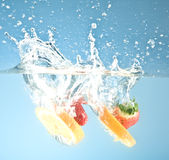 Fruits splashed into water Royalty Free Stock Photos
