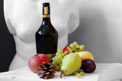 Fruits and statue. Fruits on a pedestal, and black white statue background Stock Image