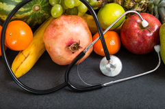 Fruits and stethoscope on stone  countertop. Royalty Free Stock Photography