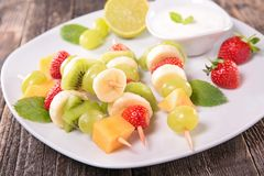 Fruits on sticks and dip Stock Images