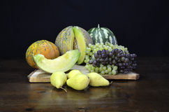 Fruits still life. Melons , watermelon, grapes and some pears on a wooden table Stock Photos
