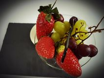 Fruits strawberry grapes whitegrapes  blackplate. Food delicious healty vegetarian sweet glass plate Stock Images