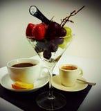 Fruits strawberry grapes whitegrapes tea coffee. Blackcoffee blackbackground martini glass Stock Photos