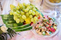 Fruits and sweets on a luxury table. Bowl of tropical fruits and plate with wedding pastry Stock Photo