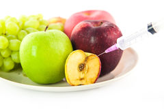 Fruits and syring on white background. Syring injected into an apple fruit Stock Photos